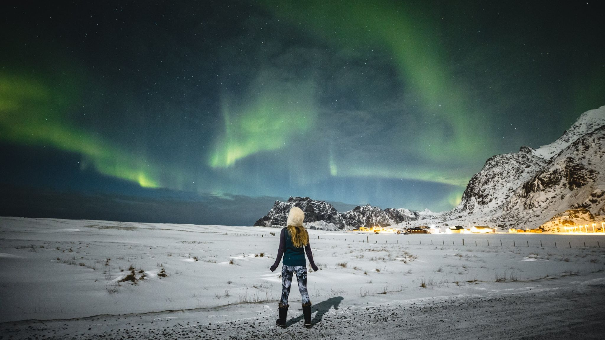 A woman stands on the pale sands of a beach in Norway looking up at the Northern Lights.